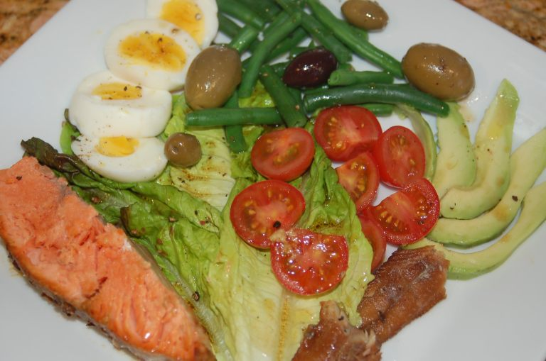 Salmon nicoise salad with cherry tomatoes, string beans, sardines, olives and soft boiled eggs.