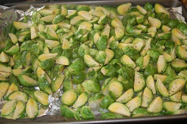 Cut the Brussels sprouts into quarters and toss in olive oil.